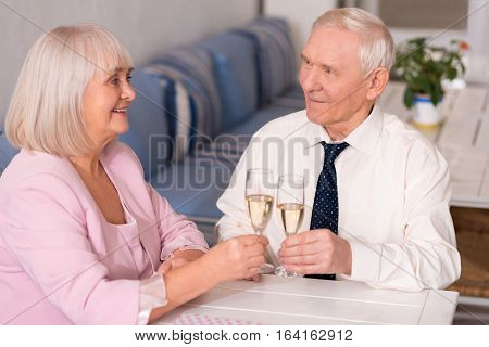 They look so happy. Enthusiastic pretty elderly lady and her companion having a glass of champagne together while casually sitting at the table in a restaurant