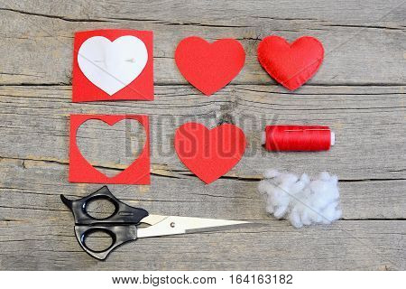 How to make a Valentine heart from a felt on Valentines Day. Sewing guide. Red felt heart, cut felt pieces in shape of a heart, paper template, scissors, thread, needle on a wooden table. Top view