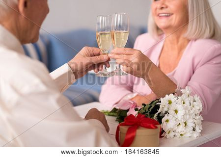 To our everlasting bound. Two energetic delighted elderly people cherishing their love while holding up glasses of champagne during anniversary celebration