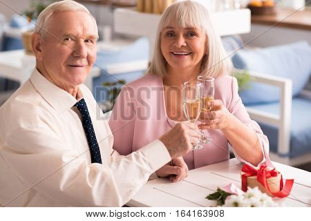 It might get dizzy. Wonderful lovely senior people having champagne during their engagement celebration in a restaurant