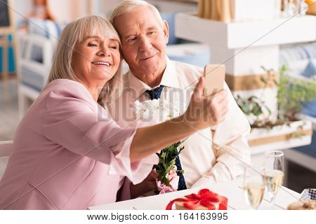 Smile and look at the camera. Beautiful happy senior couple capturing the moment of their engagement on smartphone camera during nice celebration in the restaurant