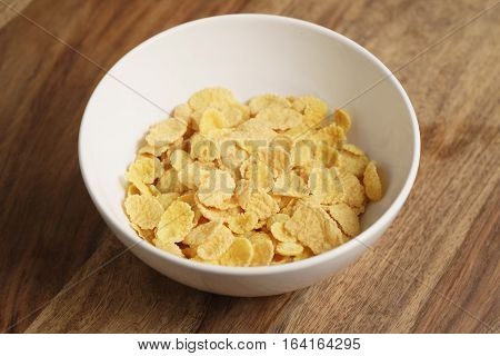 dry corn flakes in white bowl on wood table, breakfast foods