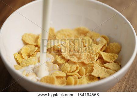 milk pour into bowl with corn flakes, preparing breakfast