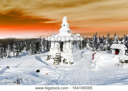 Snow covered Buddhist stupa on a mountaintop.