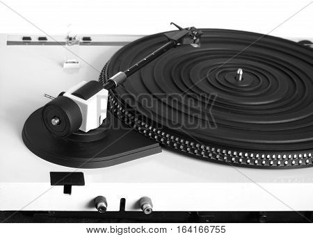 Turntable with black tonearm in silver case with rubber mat on disc with stroboscope marks with output connectors rear view isolated on white background. Horizontal view closeup
