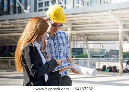 Architects are planning new project. They are working at constructions site.