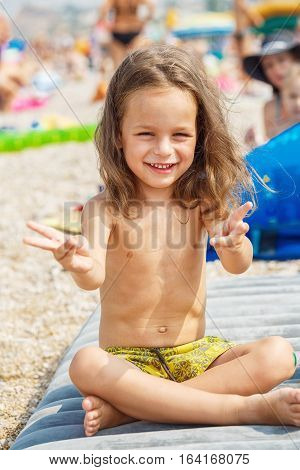 Very cute child showing peace sign on the beach
