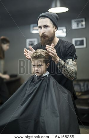 Saucy little boy in a black salon cape in the barbershop. Bearded barber with a tattoo in a black cap does kid the hairstyle. Vertical.