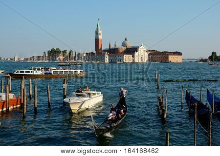 Venice Italy - September 9 2016: Gondola and boat on canal in Venice Italy. Unidentified people visible.