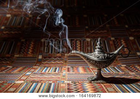 Aladdin oil lamp of oriental tales on traditional tablecloth