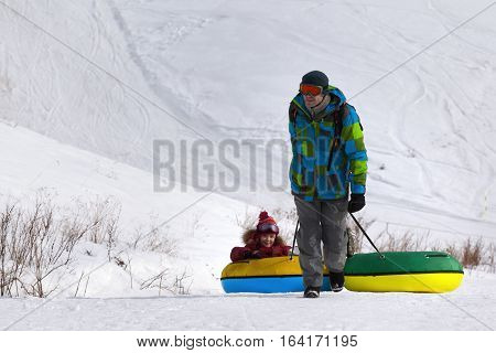 Father and daughter with snow tube at ski resort. Caucasus Mountains Georgia region Gudauri.