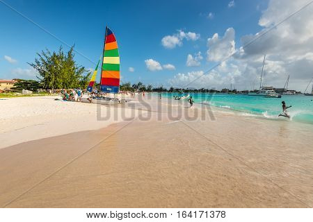 Bridgetown Barbados - December 18 2016: Brownes beach at ocean coast with people and colorful sail on a yacht at sunny day in Bridgetown Barbados.
