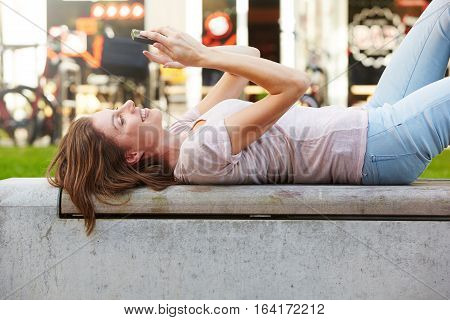 Young Woman Lying Outdoors And Using Mobile Phone