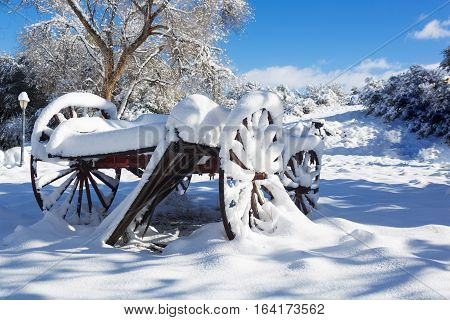 Winter Wagon Scene 01 - A winter and snowy rural scene featuring an old snow covered wagon with large wooden wheels. The background features a gas lamp, trees, and a bright blue sky with sparse clouds.