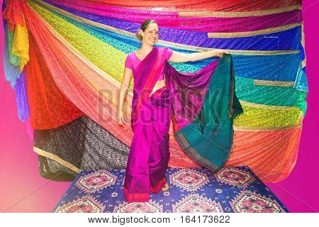 Western woman with Indian clothes. Sari. A beautiful Caucasian smiling woman dressing typical Indian clothing. Dress symbol of India: Sari. Many bright colors.
