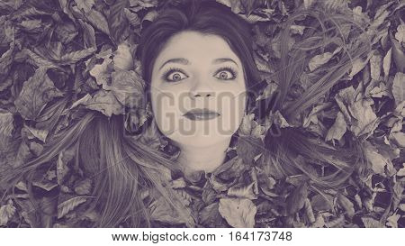 Autumn nature concept. Filtered picture with young lady in the leaves. Girl is enjoying warm weather outside.