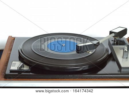 Old vintage turntable in brown wooden case with rotation vinyl record with blue label isolated on white background. Horizontal photo front view closeup