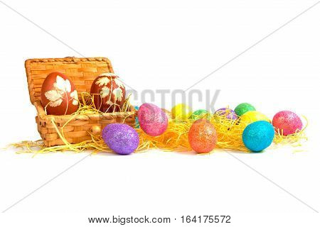 The Easter eggs in the wooden box and colorful Easter eggs near the box in hay. The Easter eggs isolated.