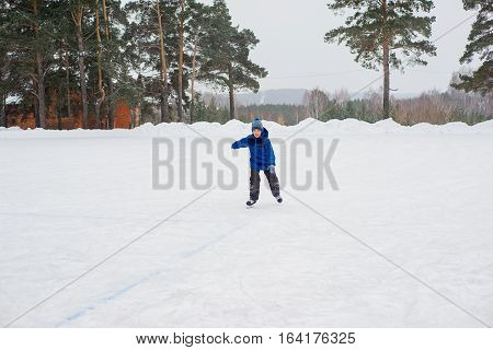 young skater boy on the ice of the frozen lake. forest on the background