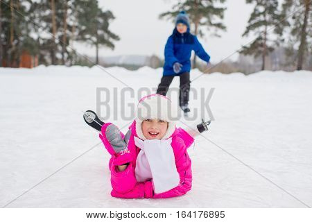 young skater girl lying on the ice of the frozen lake. boy and forest on the background