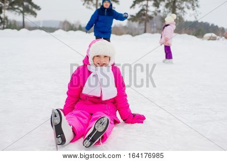 Young Skater Girl Sitting On The Ice