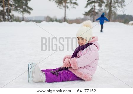 young skater girl sitting on the ice of the frozen lake. kids and forest on the background