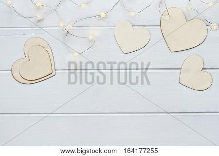 Overhead view of wooden love Valentine's hearts with lite fairy lights over a wooden background with copy space available.