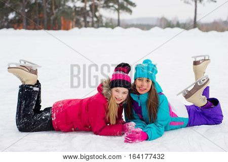 Two Attractive Skater Girls Lying On The Ice
