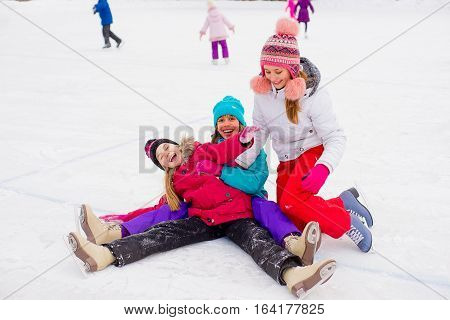 Three Attractive Skater Girl Sitting On The Ice