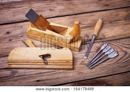Wooden planer, table from old wood, natural building materials, woodwork and antique hand tools, carrying out carpentry, tool kit for joinery, old wood texture