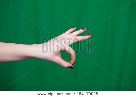 Female Hand shows ok fingers closeup on a green background