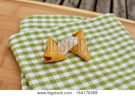 open chinese fortune cookie with blank message sitting on napkin on cutting board