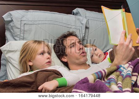 father reading bedtime story to son and daughter
