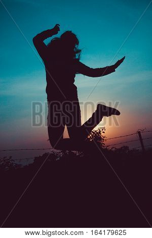 A girl Jumping as a thing of happiness during the sunset.