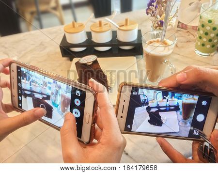 Close up people use smart phone to take picture of coffee cake before eat