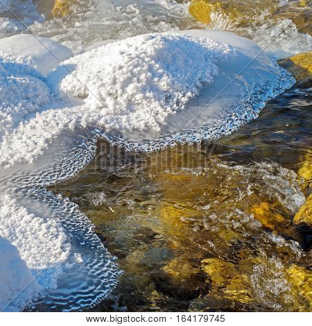 Winter stream with ice and snow decorations
