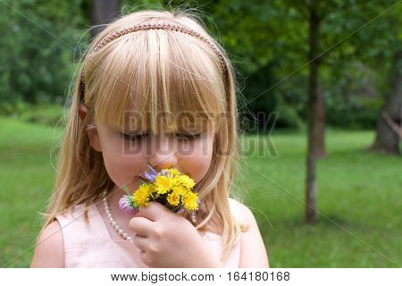 beautiful school age girl smelling flowers standing in filed outside