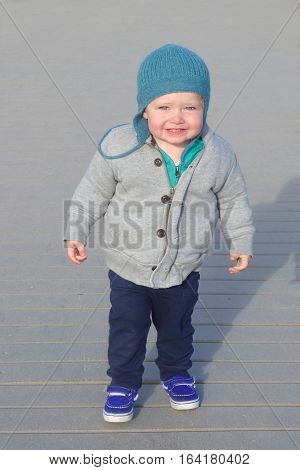 Adorable toddler boy shivering standing in sweatshirt and winter hat