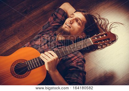 Relaxed Man On The Floor With Guitar.