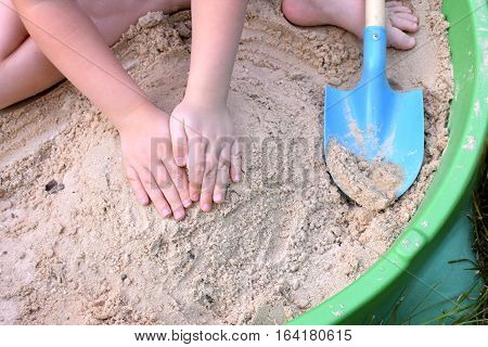 Close up of child's hands playing in sandbox