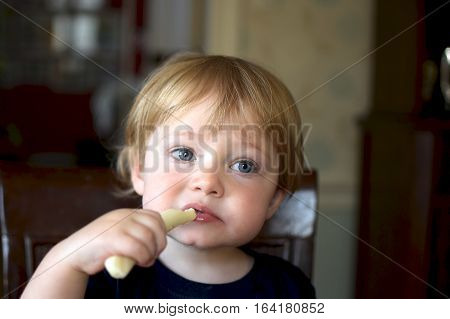 Adorable toddler boy eating string cheese for snack