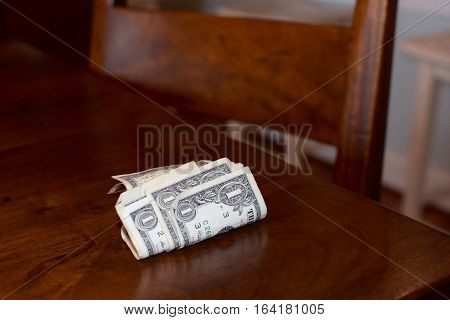 money rolled up on table showing leaving money on the table concept
