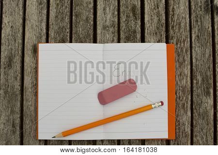notebook with number 2 pencil and eraser with the worse erase partially erased