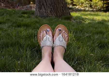 woman's feet and sandals relaxing on grass