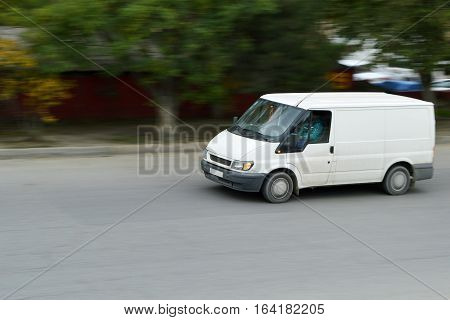 White cargo van in the motion. Blurred photo