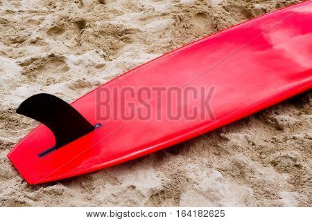 Red surfboard with black fin laying flat on sand