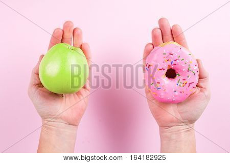 Hands choosing between apple and donut as concept of healty and unhealthy lifestyle