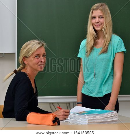 Teacher examines student with notebook at teacher's table