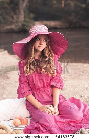 Beautiful teen girl 16 year old stylish dress and elegant hat having picnic outdoors. Looking at camera. Summer season.