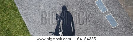 Shadow of male bicyclist walking in urban environment
